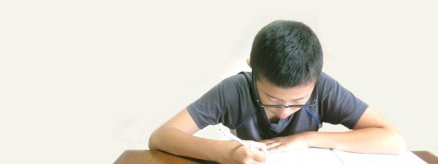必死に勉強している眼鏡をかけた男の子