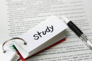 英文の上に置かれたstudyの単語帳とペン