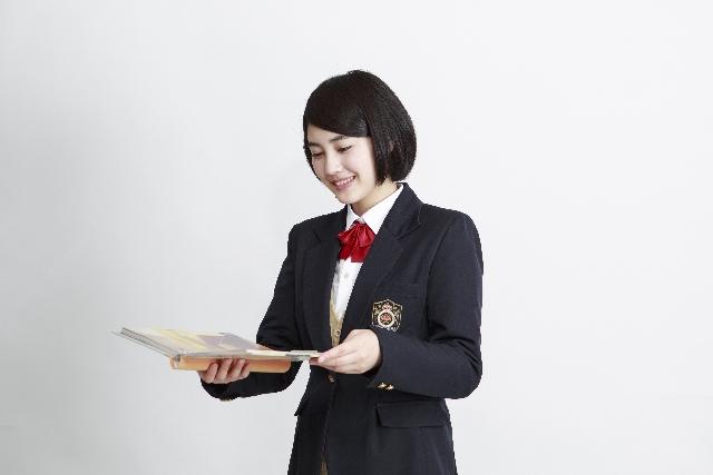 笑顔でファイルの中身を開いて見る女子高生