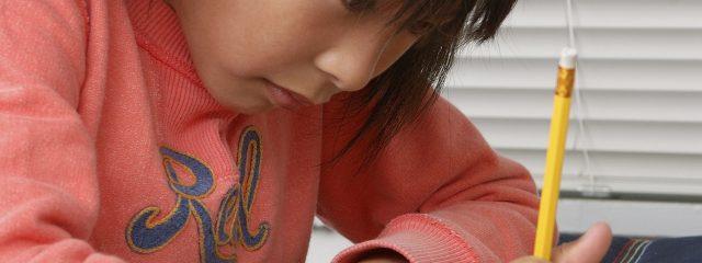 真剣な表情でノートに書き込みをする女の子