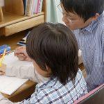男性家庭教師と勉強している男の子