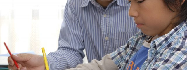 真剣に勉強する男の子と見守る男性家庭教師