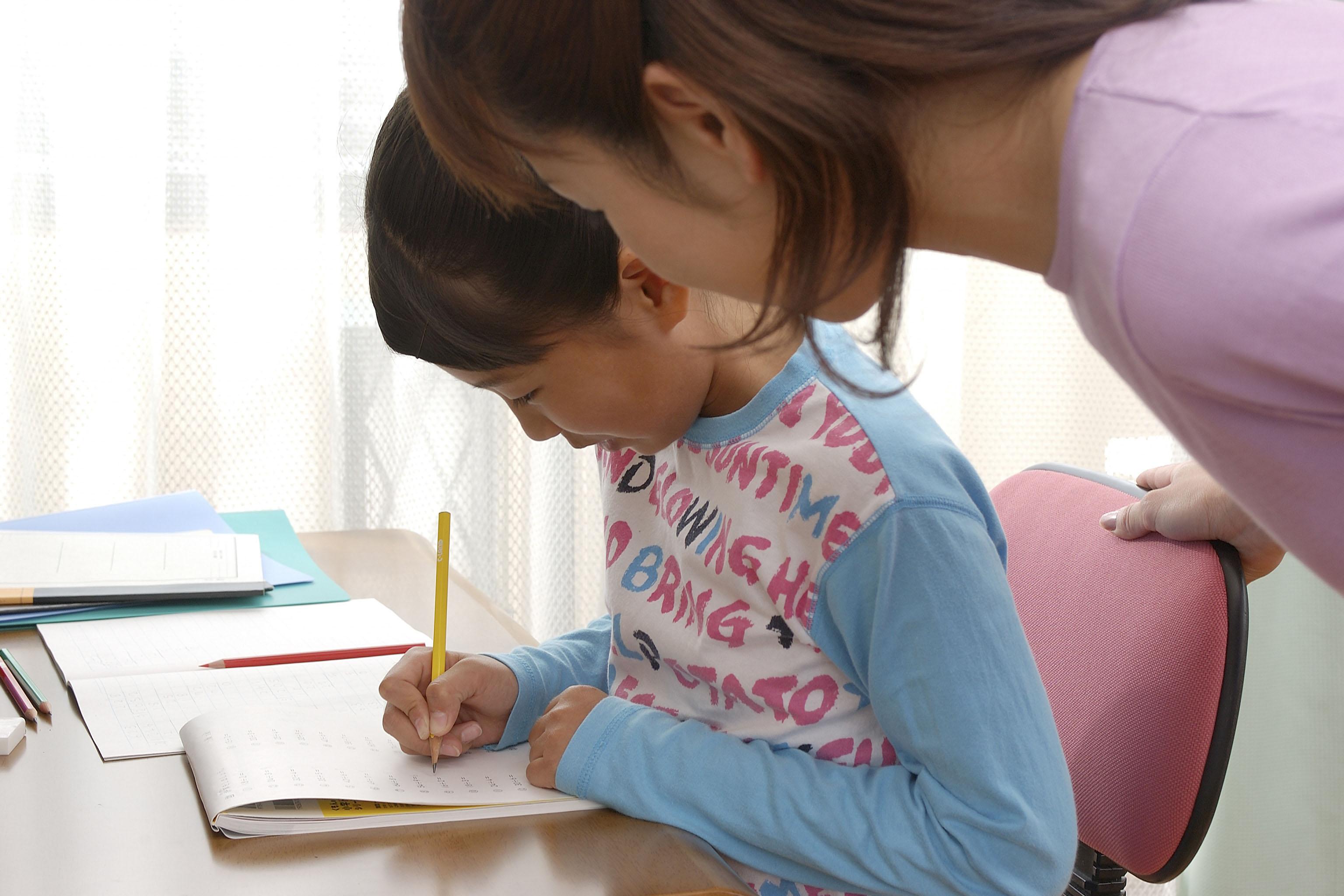 勉強する女の子に横から声をかける女性