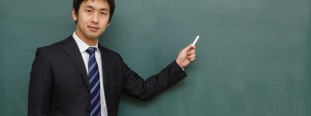 左手にチョークを持った男性が黒板の前に立っている